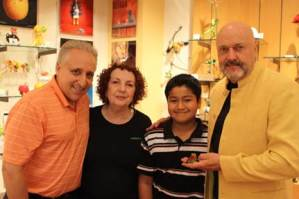"Lou Chiera, President of The Chiera Family Foundation; Joan Quinones, Gallery Manager of Pavo Real; Eduardo Gonzalez, 11-year-old N.I.C.K.'s Camp  participant; and Tim ""Frogman"" Cotterill raised money for N.I.C.K.'s Camp (Nothing's Impossible for Cancer Kids) – a summer program at the Boggy Creek Camp Facility in Eustis, Fla. for children with cancer."
