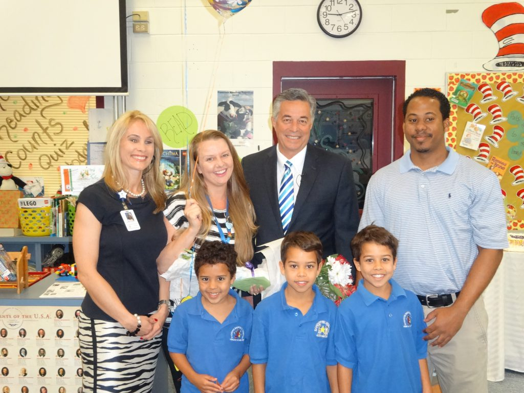 Michelle Gunning is joined by her Principal Rachel Capitano on her right and Superintendent Wayne Gent on her left and her family.