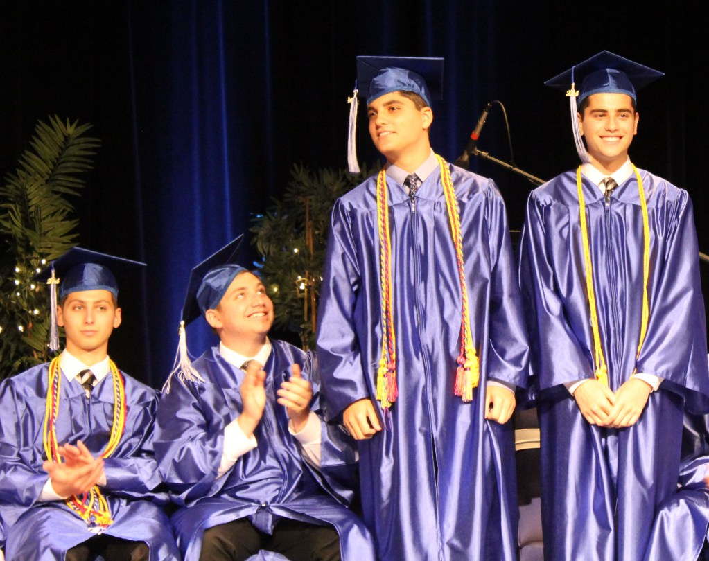 Benjamin Lewittes  and Eliyahu Moulavi applaud as Valedictorian Ethan Plotsker and Salutatorian Noah Plotsker are called to accept their honors. (Courtesy DKJA).