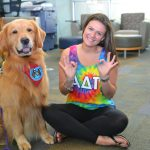 FAU student Erica Eisesser with Kol, a certified therapy dog, at FAU's Wimberly Library. (Courtesy FAU).